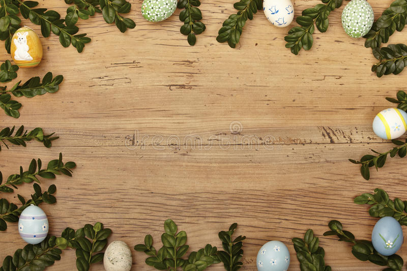 Twigs and easter eggs as frame on wood, copy space royalty free stock photography