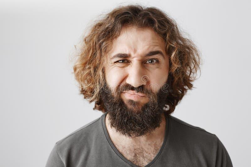 Twijfel dat het idee goed is Binnenschot van ontstemde en onzekere volwassen oostelijke kerel met baard en het krullende haar fro stock foto's