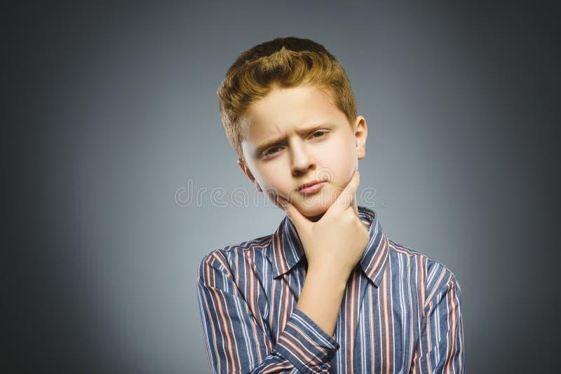 Twijfel, uitdrukking en mensenconcept - jongen die over grijze achtergrond denken royalty-vrije stock foto