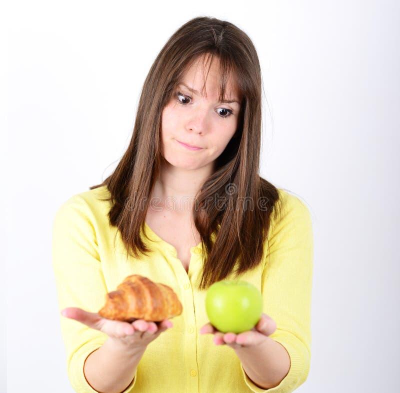 Twijfelachtige vrouw een appel en een croissant die proberend houden om w te beslissen stock foto