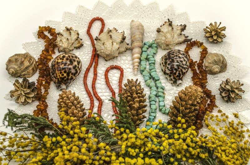 Twijgen van gele Mimosa met denneappels, overzeese shells en parels van amber, turkoois en rood koraal op gebreid van wit garen g stock afbeeldingen