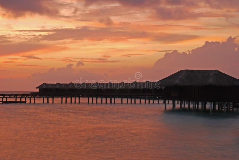 Twilight явление с бунгалом Overwater и драматическим небом стоковые изображения