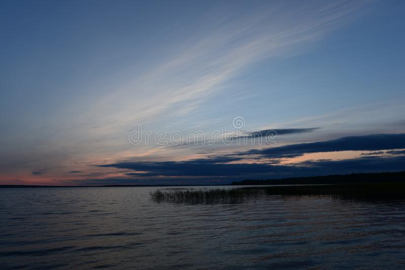 Twilight blue sky in cirrus clouds at sunset in a dark blue cloud on the horizon above the water of the lake. Blue sky in cirrus clouds at sunset in a dark blue stock photos