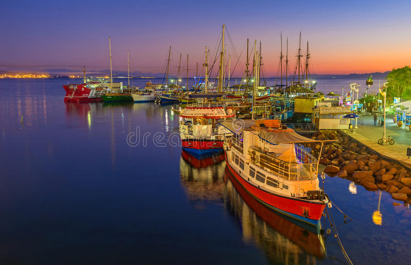 The twilight in Eilat port. EILAT, ISRAEL - FEBRUARY 24, 2016: The yachts and pleasure boats surrounded by colorful twilight sky and brightly illuminated water royalty free stock image