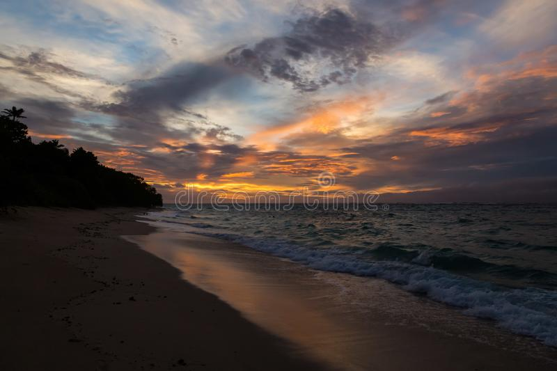 Twilight evening sunset. Waves, surf, swash at empty beautiful sandy beach on Foa island, Haapai, Tonga, Polynesia, Oceania. stock image
