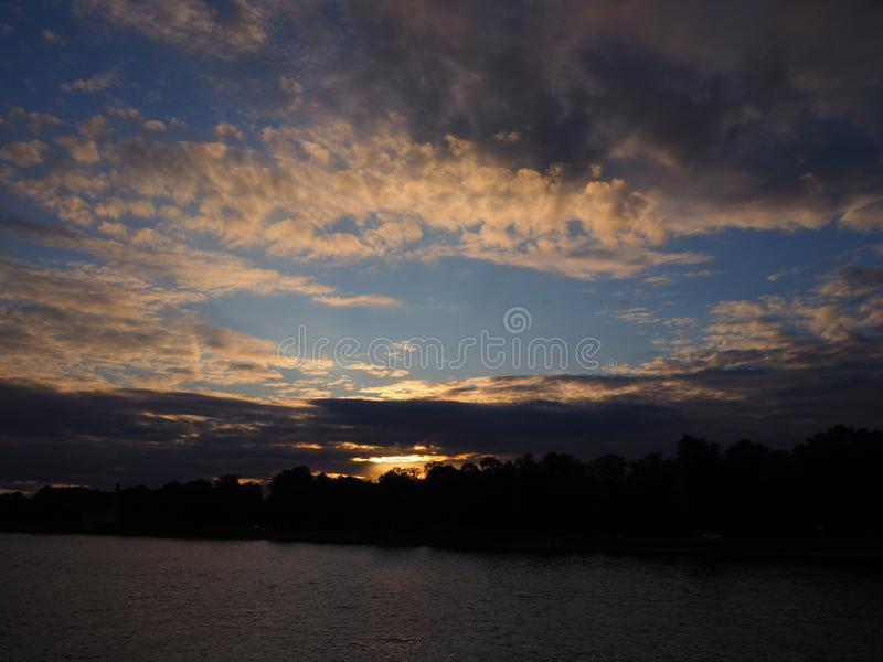 Twilight landscape of sun sets over the forest on a riverbank, blue sky covered with dark thunder clouds stock photos