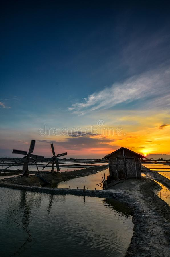 Twilight at the place of manufacture of salt. Sun, sunset, sunrise, windmill, bluesky, hut royalty free stock images