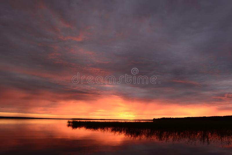 Twilight sky in the bright glow of sunset over the calm water of the lake. Dusk landscape Twilight sky in the bright glow of sunset over the calm water of the stock image