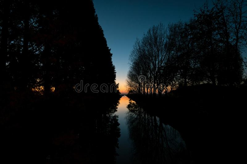 Twilight sky over a dutch canal. Trees are silhouetted against the sky and reflected in the water. Twilight sky over a canal in Holland. Trees are silhouetted stock images