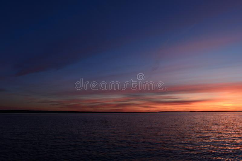 Twilight sunset glow in a cloudy haze of nightfall bright blue sky on the horizon above the water of the lake. Sunset photography Twilight sunset glow in a royalty free stock photography