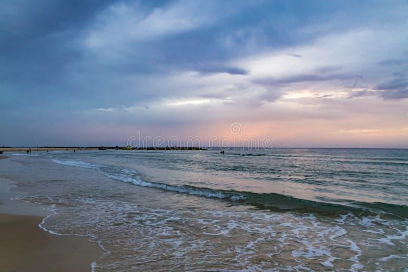 Twilight time at the beach in Netanya, Israel, Mediterranean sea. Overcast sky, foam and waves royalty free stock photo