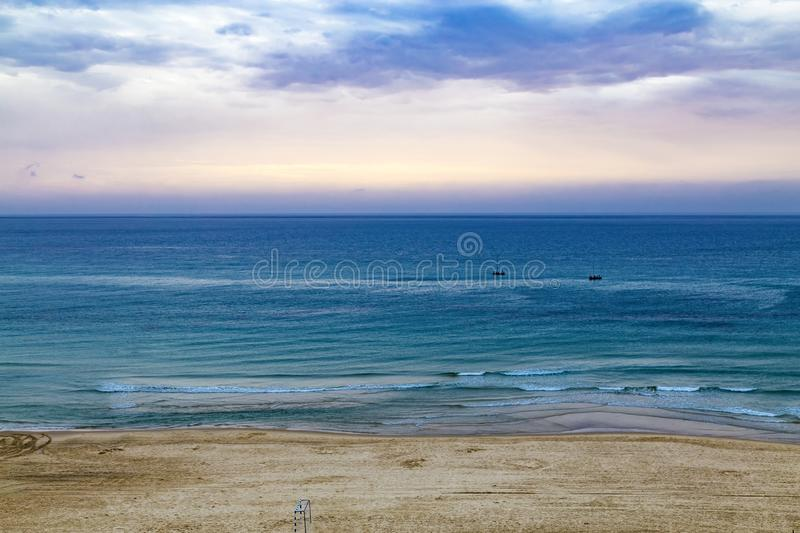 Twilight time and sunset at the beach in Netanya, Israel, Mediterranean sea. Overcast sky, foam and waves. Aerial view. 2 boats in. The sea royalty free stock images