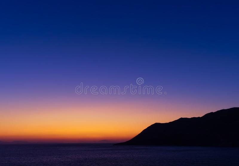 Twilight vibrant colorful sky above sea and mountain sihlouette at dusk time stock photo