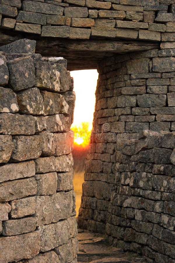Twilight at Zimbabwe ruins. The last light of the sun shining through a stone archway at the great Zimbabwe ruins stock images