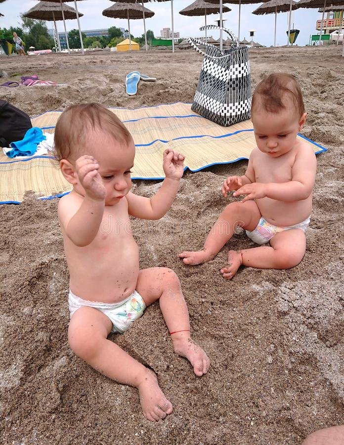 Twin babies playing in the sun-beach time stock photos