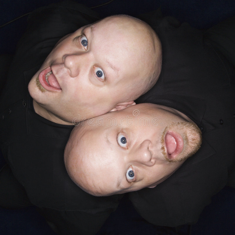 Twin bald men. Aeriel view of Caucasian bald identical twin men sitting back to back making facial expressions stock photos