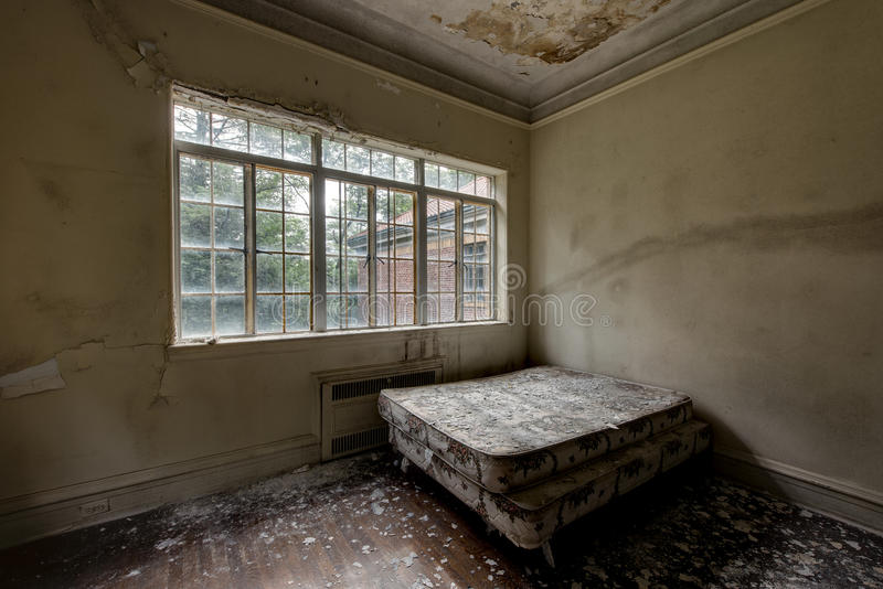 Twin Bed with Window & Hardwood Floors - Abandoned Mansion stock images