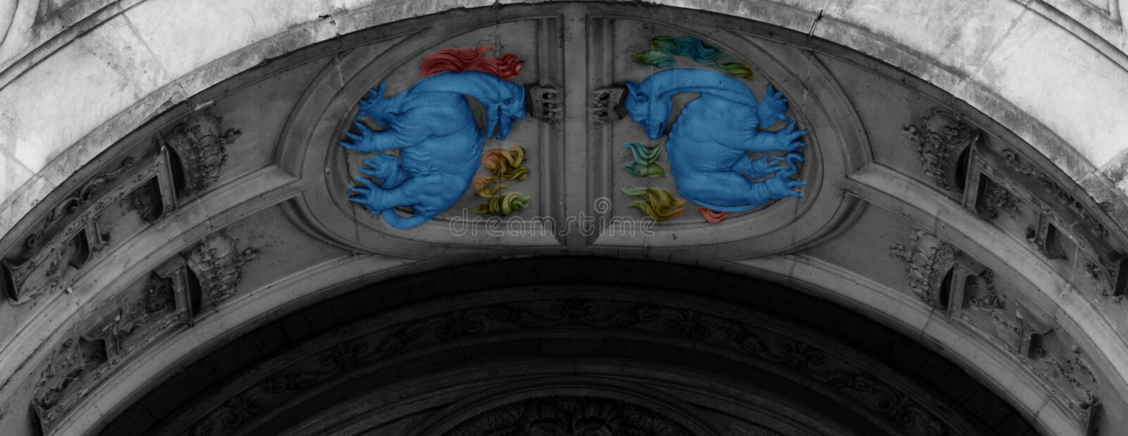 Twin blue dragons inside the arch. Shot in black and white  and painted in colors detail on the facade of this historic building representing some character stock image