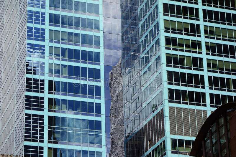Twin Blue Skyscrapers. Twin skyscrapers with blue toned plate glass window facade in city central business district royalty free stock images