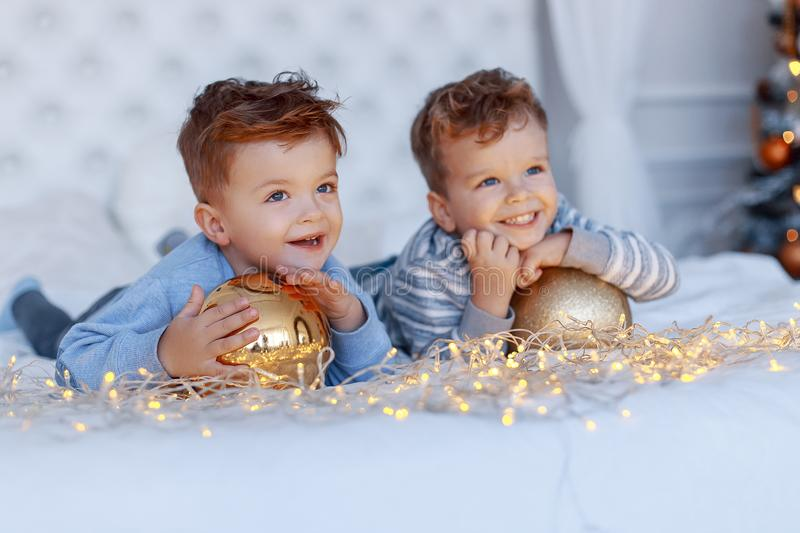 Twin brothers in front of the christmas tree with candles and gifts. love, happiness and big family concept stock photos