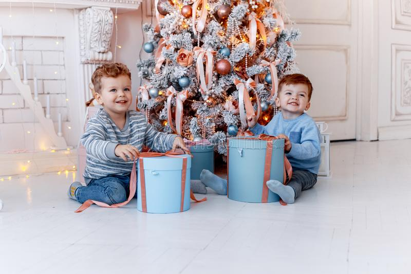 Twin brothers in front of the christmas tree with candles and gifts. love, happiness and big family concept stock images