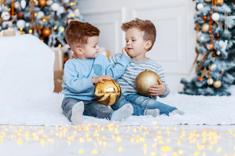 Twin brothers in front of the christmas tree with candles and gifts. love, happiness and big family concept royalty free stock photo