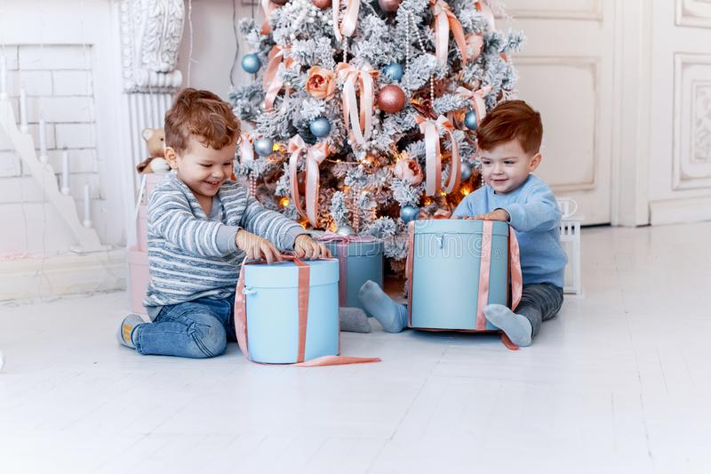 Twin brothers in front of the christmas tree with candles and gifts. love, happiness and big family concept stock photography