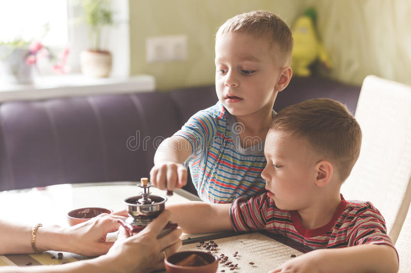 Twin brothers helping her mother to grind coffee royalty free stock photos