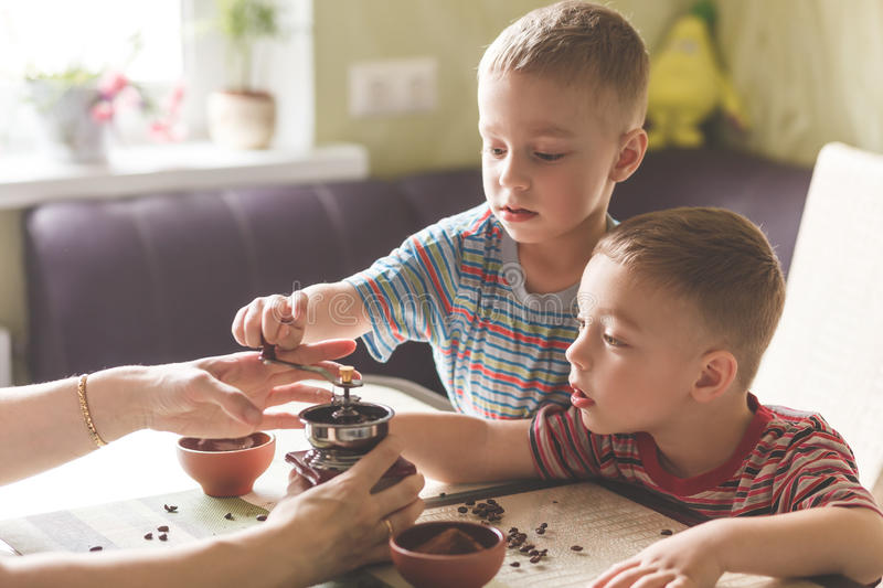 Twin brothers helping her mother to grind coffee stock photography