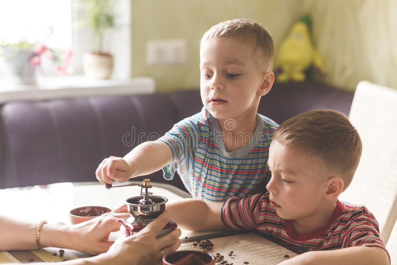Twin brothers helping her mother to grind coffee royalty free stock images