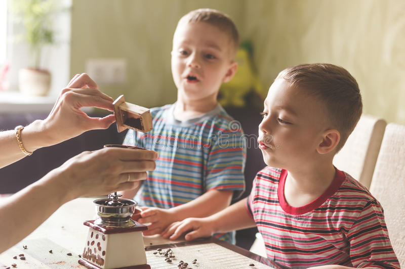 Twin brothers helping her mother to grind coffee. In the kitchen in the morning royalty free stock images
