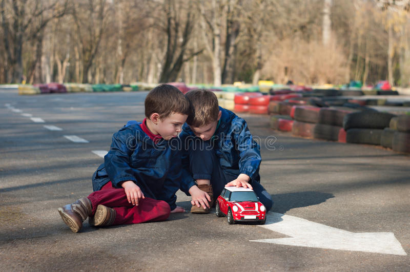 Twin brothers play with a toy car royalty free stock photos
