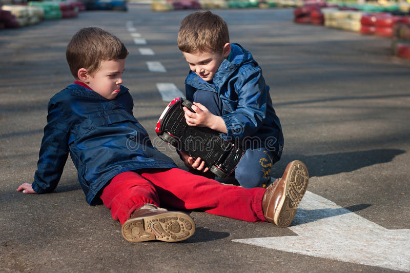 Twin brothers play with a toy car stock photography