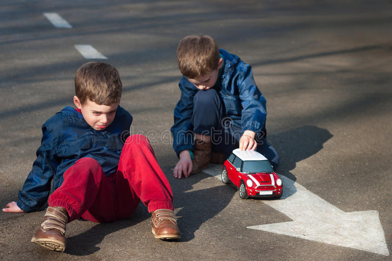 Twin brothers play with a toy car stock images