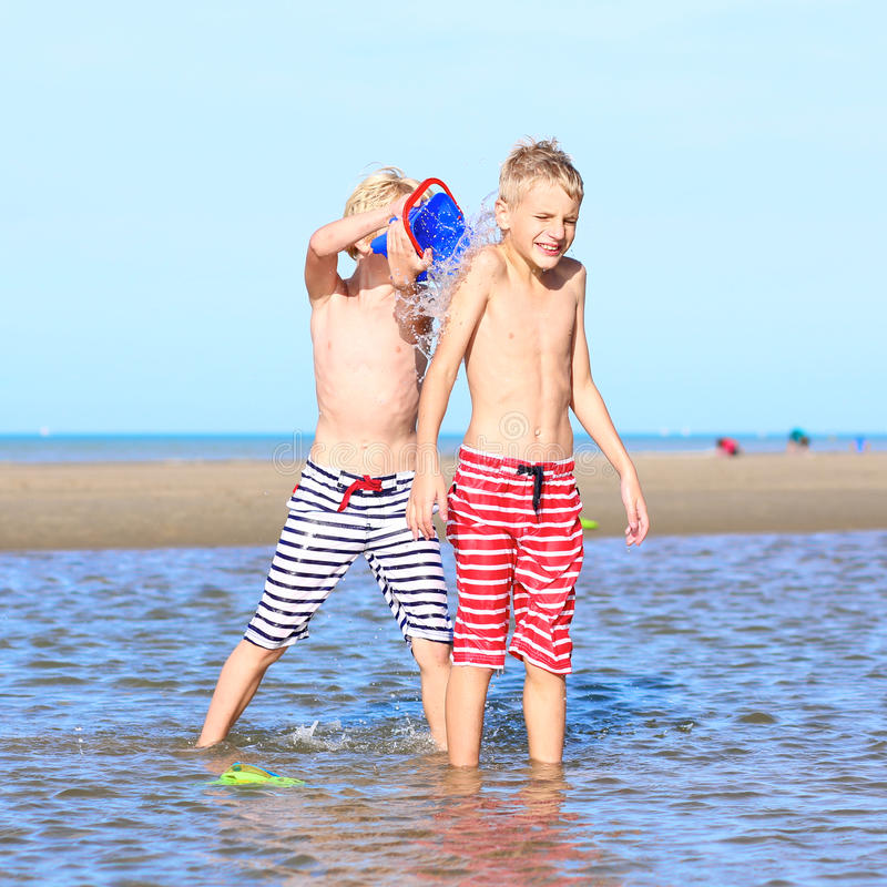Twin brothers playing on the beach. Two happy laughing kids, teenage boys, twin brothers, having fun at the North Sea playing together on the beach, running and stock photos