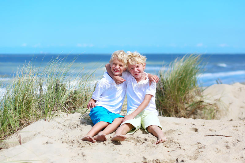 Twin brothers playing on the beach royalty free stock image