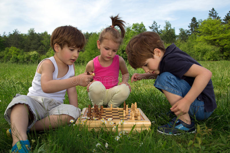 Twin Brothers Playing Chess In The Park While Cute Little Girl Watching The Game royalty free stock image