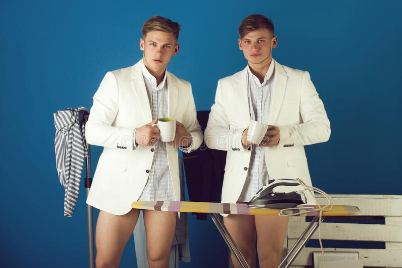 Twin brothers with serious faces. Ironing board with iron and clothes rack on blue background. Fashion concept. Men with cups in dressing room. Businessmen stock photos