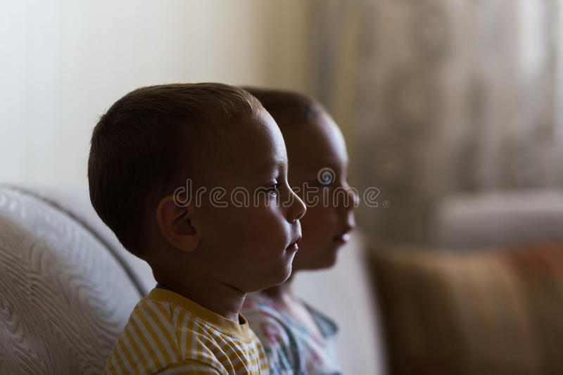 Twin brothers sitting on sofa stock images
