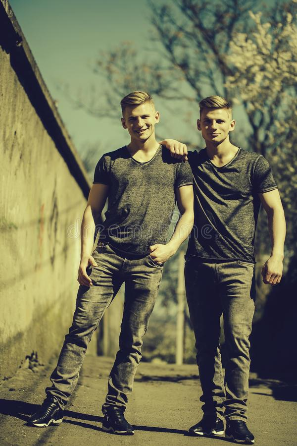 Twin brothers smile outdoor. Twin brothers young handsome friendly blond men in jeans hug and smile outdoor on streetscape background stock images
