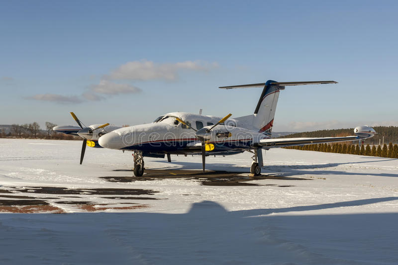 Twin engine aircraft with turboprop power plant under snow in sunny winter day. Twin engine aircraft with turboprop power plant on runway under snow in sunny royalty free stock images
