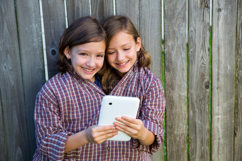Twin Girls Dressed Up Pretending Be Siamese And Tablet Pc Stock Photo