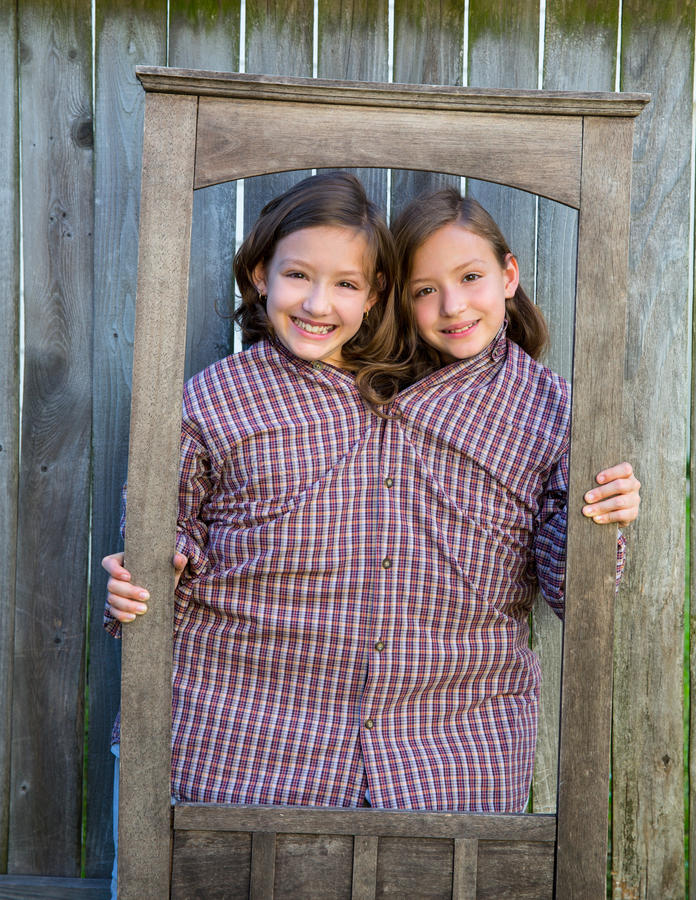 Twin girls fancy dressed up pretending be siamese in frame. Twin girls fancy dressed up pretending be siamese with dad shirt playing with grunge border frame royalty free stock photo