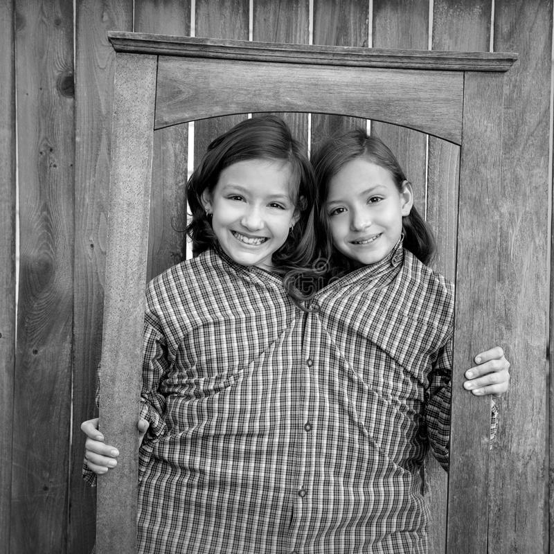 Twin girls fancy dressed up pretending be siamese in frame. Twin girls fancy dressed up pretending be siamese with dad shirt playing with grunge border frame stock images