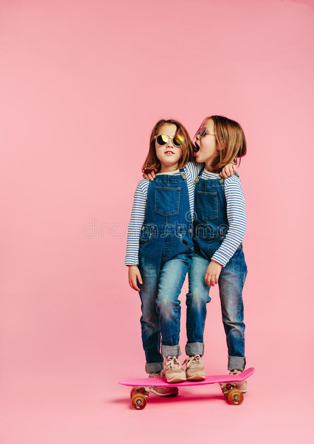 Twin girls together with skateboard stock photo
