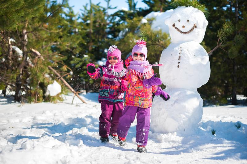 Twin girls in the winter in the woods for a walk near a large snowman. Children in pink jackets and glasses in the sun jumping. Two twin girls in the winter in stock photo