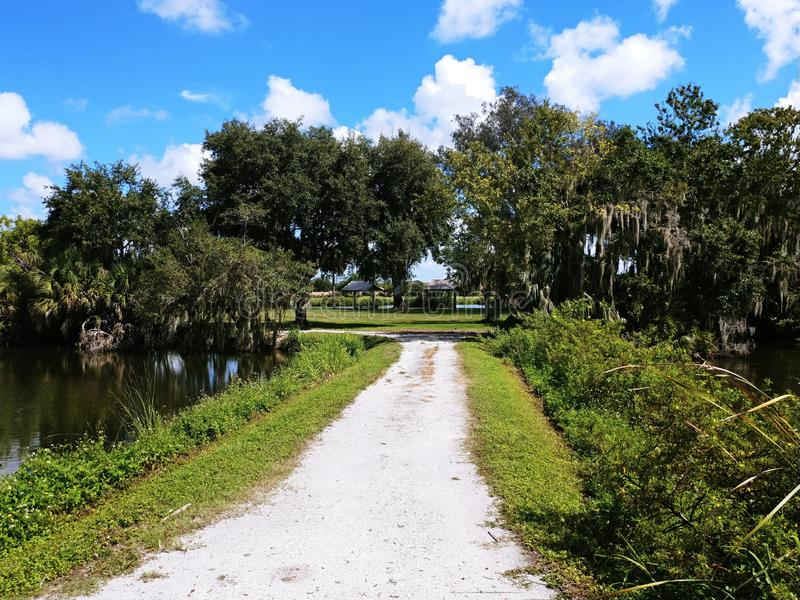 Twin Lakes Park in Sarasota Florida under a bright sunny blue sky with white fluffy clouds a lake and trees. Twin lakes park in Sarasota Florida, with live oak royalty free stock photo