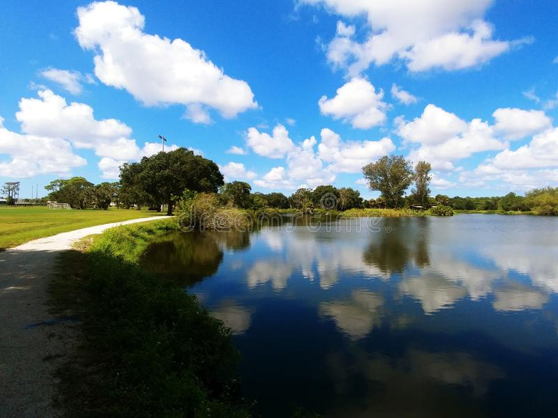 Twin Lakes Park in Sarasota Florida under a bright sunny blue sky with white fluffy clouds a lake and trees. Twin lakes park in Sarasota Florida, with live oak royalty free stock photography