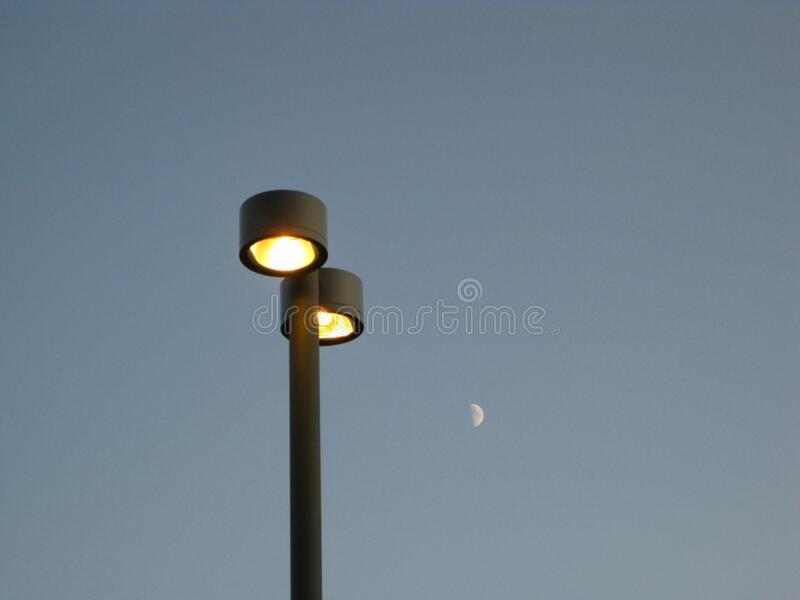 twin-lamp-post-and-half-moon-in-the-background stock photo