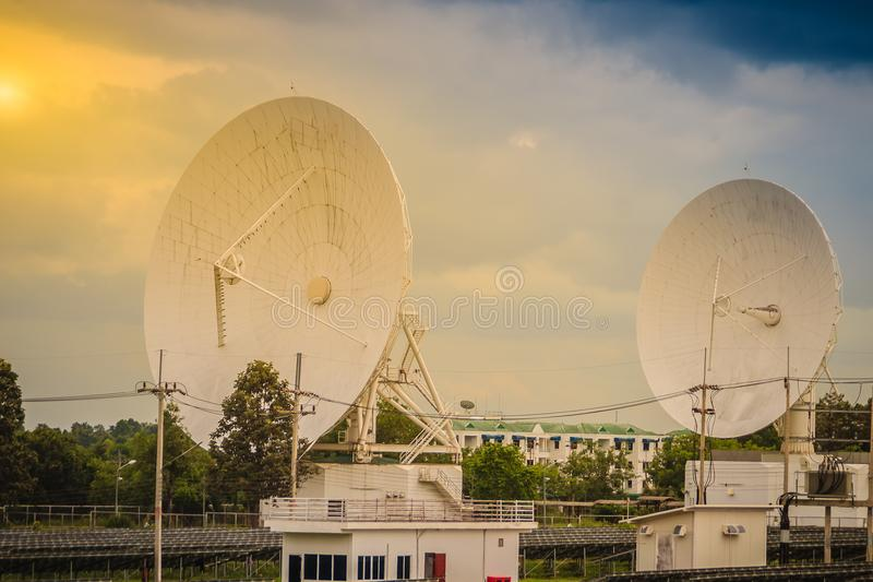 Twin large scale white satellite dish in solar farm under dramatic blue and cloudy sky background. royalty free stock photography